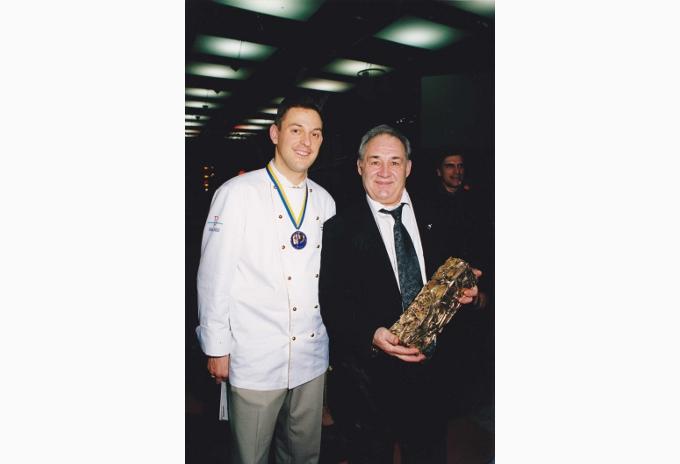 Guy Bardel tenant le précieux Trophée du Bocuse d'Or, gagné par son ami François Adamski